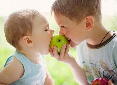 Фото Два маленьких мальчика едят одно яблоко