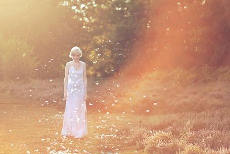 Фото Девушка в белом платье стоит в падающих перьях (© Штушка), добавлено: 02.12.2011 00:27