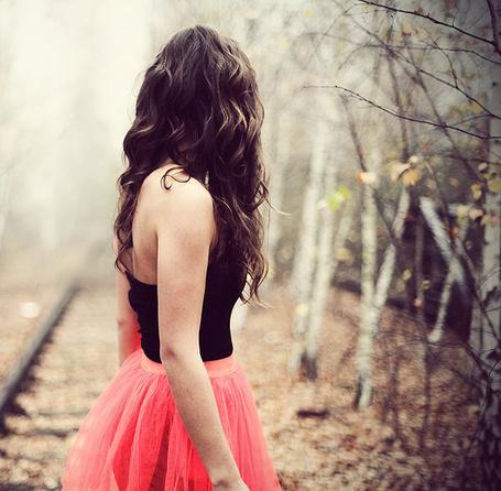 Фото Шатенка в яркой юбке и чёрной кофте стоит  около железнодорожных путей