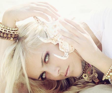 Фото Блондинка с красивыми браслетами на руках приложила раковину к уху