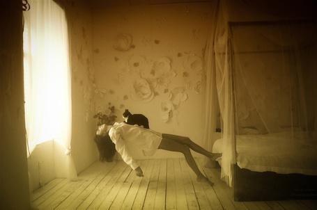 Фото Девушка парит в комнате возле кровати,на ней сидит кот