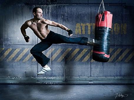 Фото Парень в прыжке бьет по боксерской груше ногой
