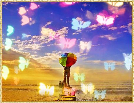 Фото Девушка с разноцветным зонтом стоит на помосте глядя в море