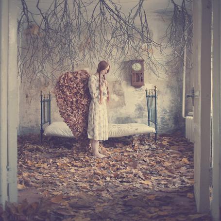 Фото Рыжая девушка стоит в комнате усыпанной осенними листьями, из этих листьев у нее за спиной склеены ангельские крылья (Анка Журавлева)
