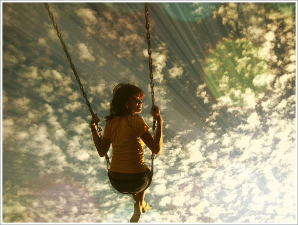 Фото Девушка катается на качелях на фоне солнечного неба