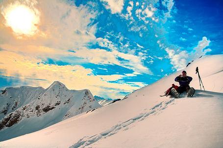 Фото Мужчина-лыжник сидит на вершине заснеженной горы