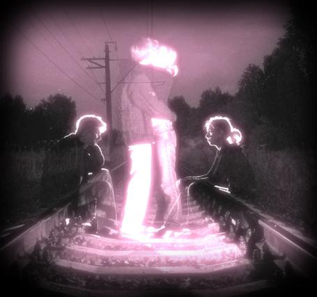 Фото Девушка и парень сидят на рельсах друг напротив друга, представляя, что целуются