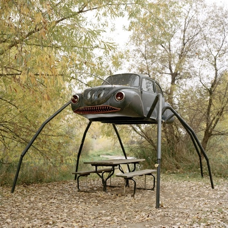 Фото Автомобиль - монстр на паучьих лапах, над столиком и скамейками, фотограф Энни Коллинж / Annie Collinge