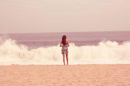 Фото Девушка стоит у набегающих на пляж морских волн