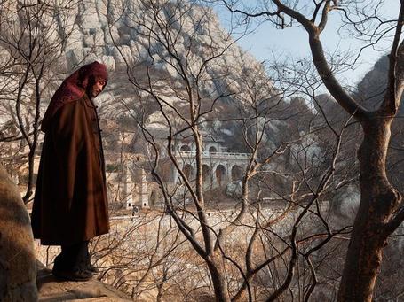 Фото Буддийский монах стоит на камне, National Geographic 2011