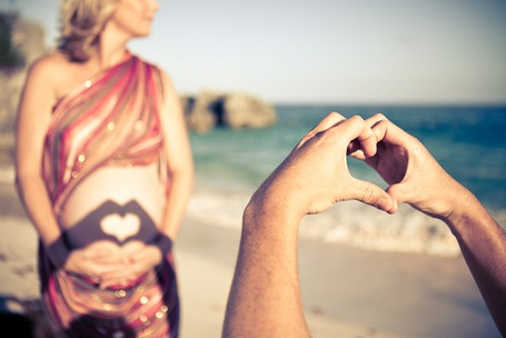Фото Парень руками показывает 'сердечко', а тень падает на живот девушки