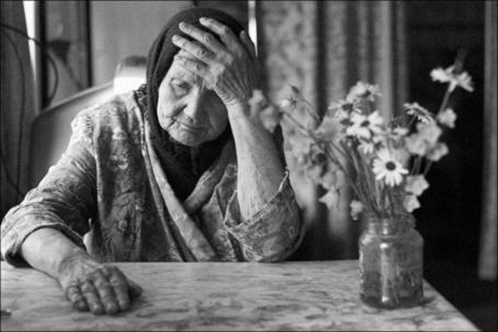 Фото Бабушка сидит за столом и держится за голову