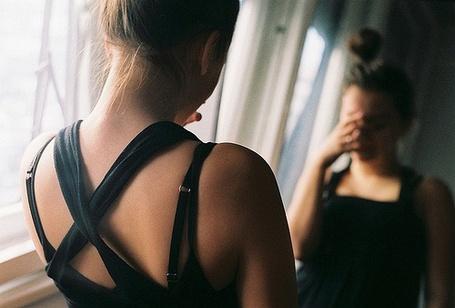 Фото Плачущая девушка смотрит в зеркало