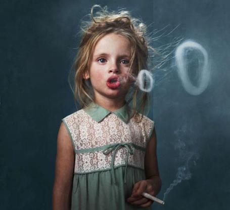 Фото Девочка  курит и пускает дымные колечки