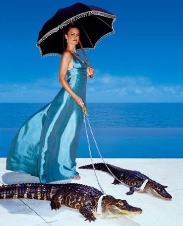 Фото Женщина под зонтиком выгуливает по пляжу двух крокодилов