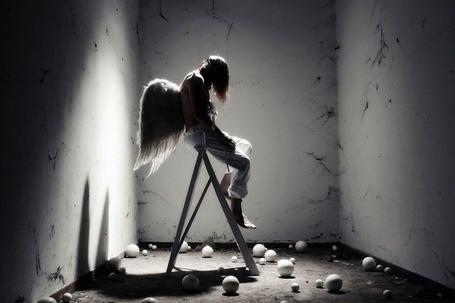 Фото Грустный ангел сидит на стремянке в комнате без дверей