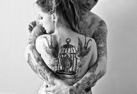 Фото Парень с девушкой в татуировках стоят обняв друг друга