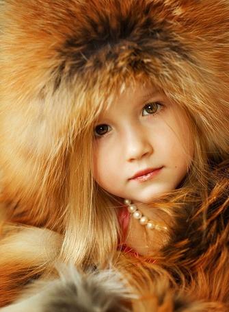 Фото Маленькая девочка позирует с лисьей шапкой на голове