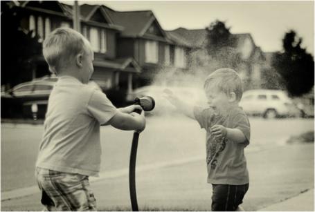 Фото Мальчик окатил друга водой из шланга