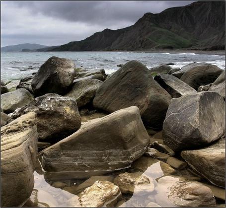 Фото Нагромождение валунов, о которые бьются морские волны, горы и серое небо (© Anatol), добавлено: 17.04.2012 13:40