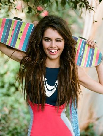 Фото Девушка с полосатым скейтом в руках игриво подмигивая показывает кончик языка