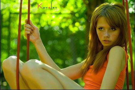 Фото Рыжая девушка с веснушками сидит на качелях на фоне зеленых листьев (Фотограф Коvalev)