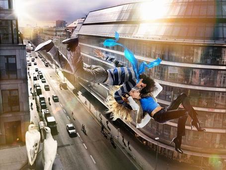 Фото Девушка с парнем, обнимаясь, плывут в небе над городом