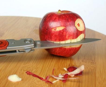 Фото Яблоко, почищенное как рожица, держащая в зубах нож (© INFERI), добавлено: 27.04.2012 11:38