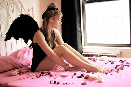 Фото Грустная девушка с чёрными крыльями сидит на розовой кровати в лепестках роз