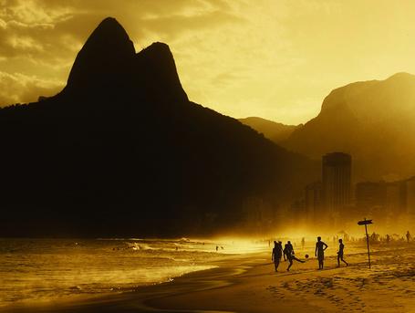 Фото Парни играют в футбол на городском пляже, фотограф Isac Goulart