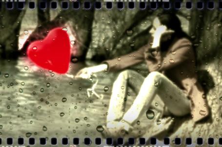 Фото Девушка сидит у реки держа в руке красный воздушный шар в форме сердечка