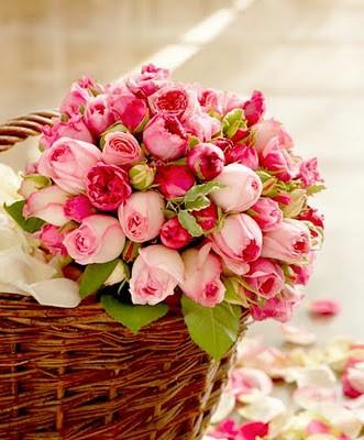 Фото Букет из роз и тюльпанов лежит в плетёной корзине