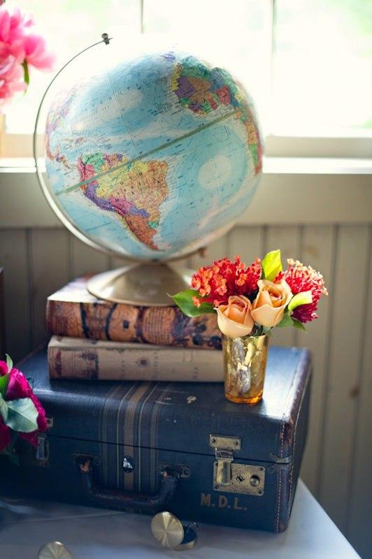 Фото Чемодан, на котором лежат книги, на которых стоит глобус, и ваза с цветами