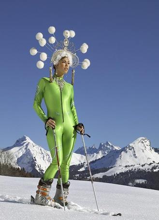 Фото Девушка на лыжах в странном головном уборе на фоне заснеженных гор