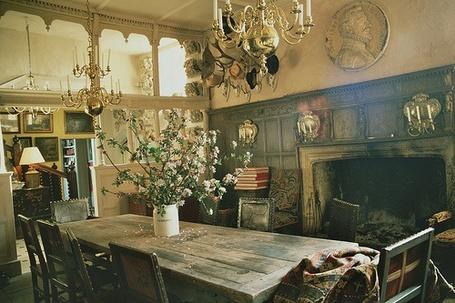 Фото Комната со столом посередине, на котором стоит ваза с цветами, камином, старинными люстрами