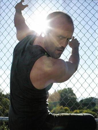 Фото Американский и английский актер Джейсон Стэтхэм / Jason Statham в лучах солнца  вцепился в сетку