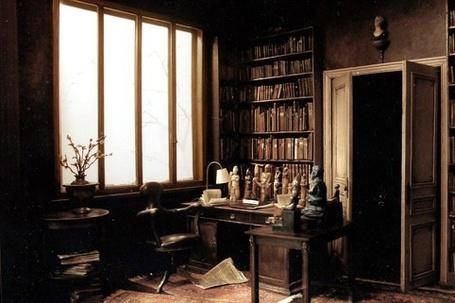 Фото Кабинет: шкаф с книгами, стол, заставленный статуэтками, журнальный столик, на котором стоит ваза с цветами