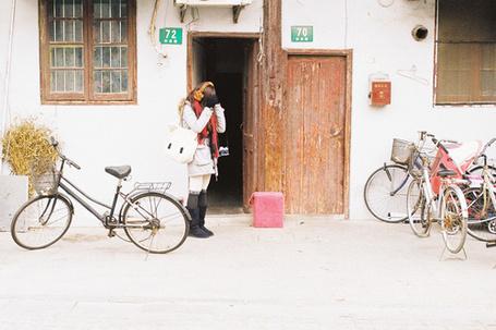 Фото Растроенная девушка, поднесшая руки к глазам стоит возле входа в здание