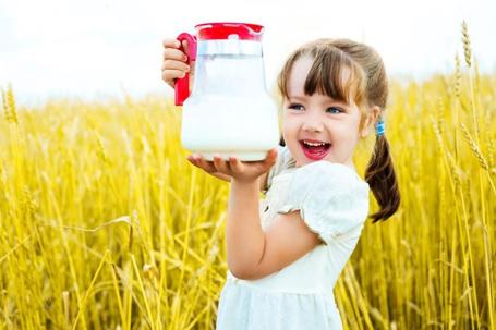 Фото Девочка в поле держит в руках кувшин с молоком