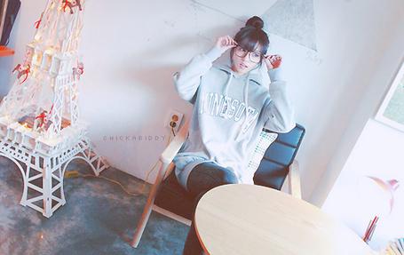 Фото Азиатка в толстовке сидит в кресле в комнате, где есть макет Эйфелевой Башни, и придерживает очки руками