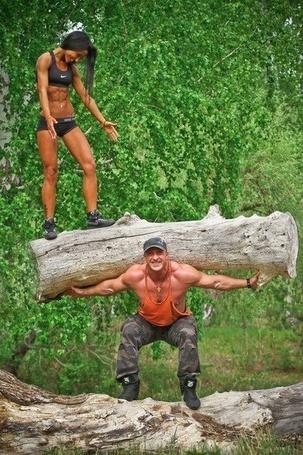 Фото Мужчина поднял бревно со стоящей на нем девушкой