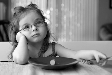 Фото Девочка в очках в задумчивости сидит с вилкой за столом