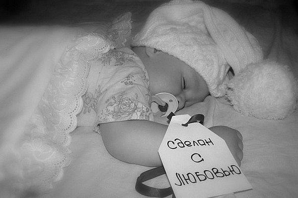 Фото Малыш спит в шапочке и с соской во рту, на руке бирка с надписью 'Сделан с любовью'