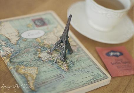 Фото Натюрморт с сувенирной фигуркой Эйфелевой башни, стоящей на карте мира, рядом чашка чая. Фотограф Claire Brocato (© Natko), добавлено: 03.08.2012 12:11