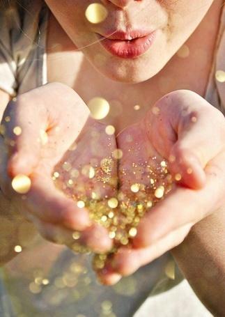 Фото Девушка сдувает с ладоней золотистую пыльцу