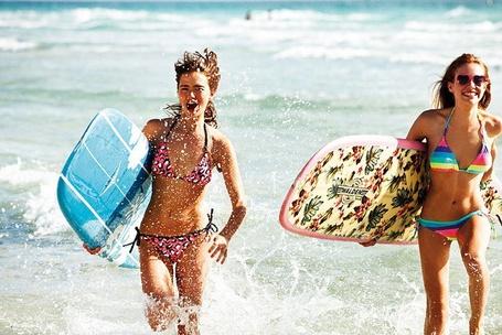 Фото Счастливые девушки выбегающие из воды с досками для серфинга