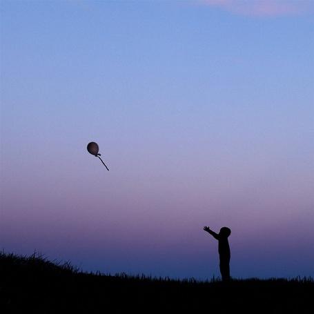Фото Силуэт мальчика отпускающего воздушный шарик в небо