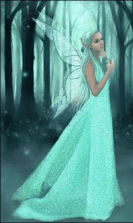 Фото Лесная фея в бирюзовом платье с цветком в руке прогуливается в лесу