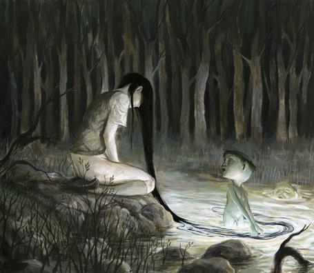 Фото Мальчик, стоящий в воде, держит за волосы девушку, сидящую на берегу