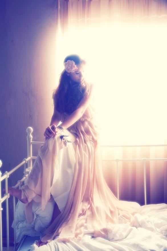 Фото Девушка, с цветком на голове,  в длинном  бело-розовом платье, сидит на спинке кровати, фотограф Tina Patni